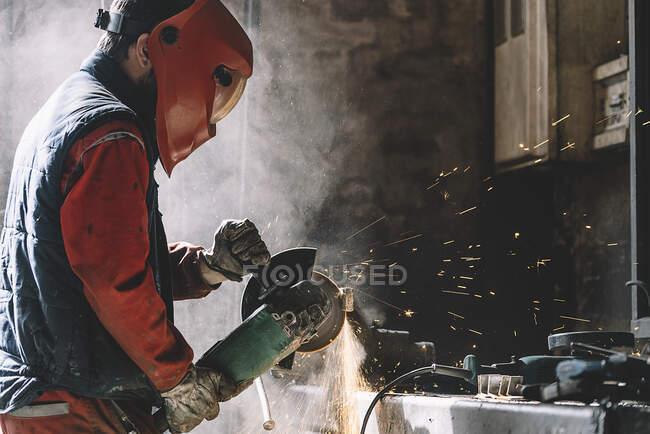 Mann arbeitet mit Schleifer, der Metall schneidet. — Stockfoto