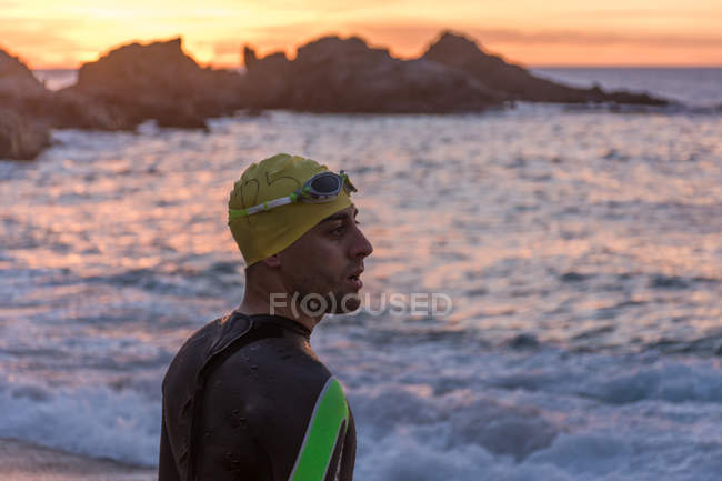 Triathlete standing on beach — Stock Photo