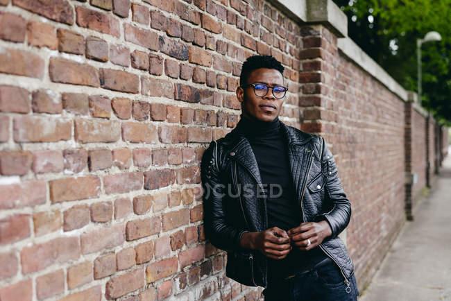 Hombre negro apoyado en la pared de ladrillo - foto de stock