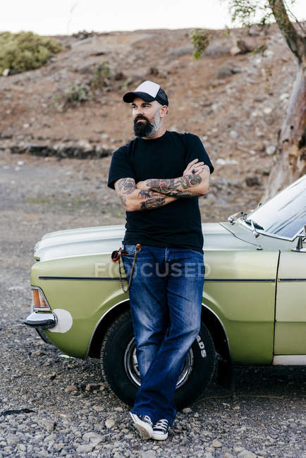 Tattooed man leaning on car — Stock Photo