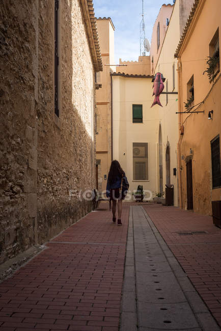 Girl with backpack walking on street — Foto stock