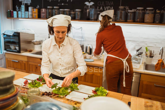 Cook preparing salad on kitchen — Stock Photo