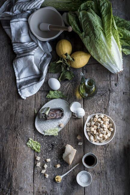 Lot de divers ingrédients pour un délicieux plat couché sur une vieille table de bois près du mortier et du pilon. — Photo de stock