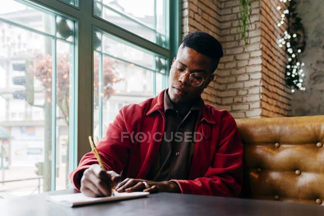 Schwarzer Mann im Café sitzen und schreiben — Stockfoto