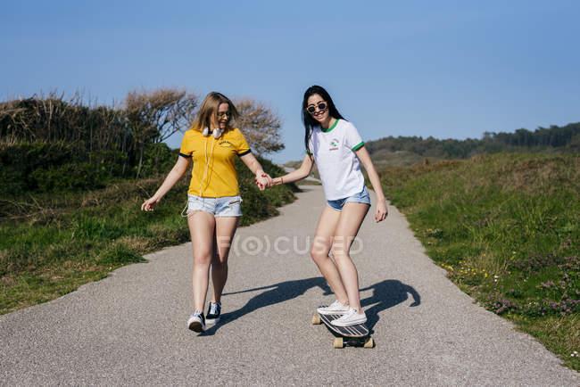 Amigas com skate em estrada rural — Fotografia de Stock