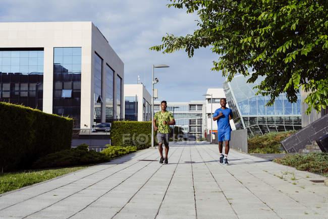 Etnia homens correndo juntos na rua moderna — Fotografia de Stock