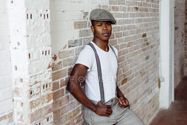 Black man in front of brick wall — Stock Photo