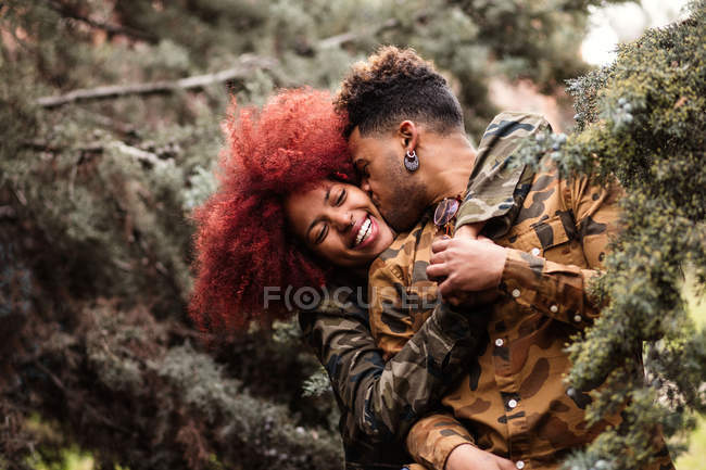 Laughing couple kissing among trees — Stock Photo