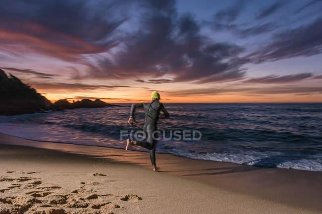Triathlete running on sandy beach — Stock Photo