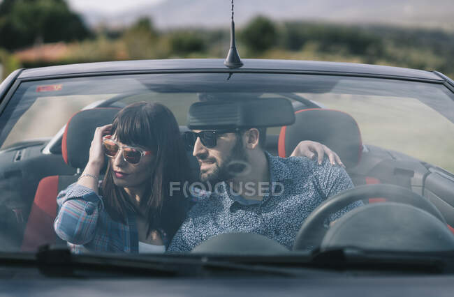 Man and woman travel in convertible car. — Stock Photo