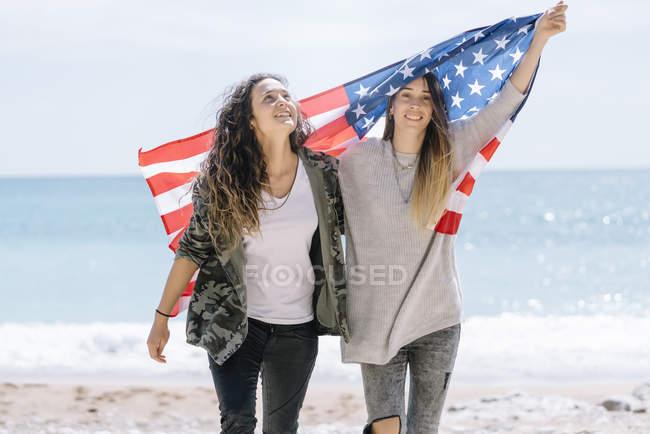 Duas jovens mulheres adultas posando na praia com bandeira dos EUA . — Fotografia de Stock