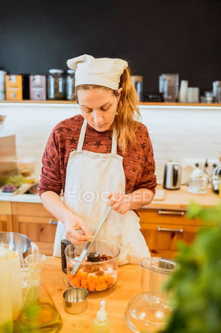 Cook putting ingredients to blender — Stock Photo