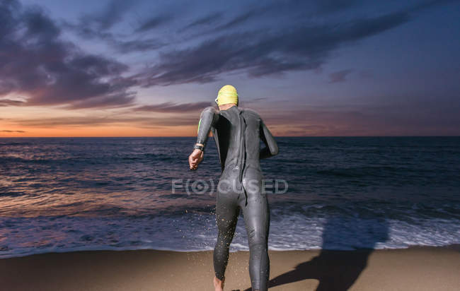 Triathlete running in sandy beach — Stock Photo