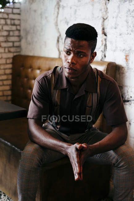Человек в классической одежде сидит в кафе — стоковое фото