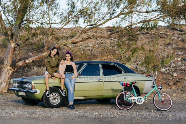Mujeres posando en coche verde - foto de stock