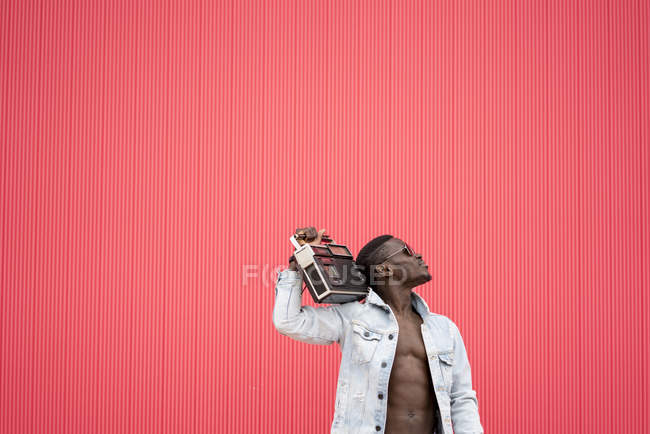 African american man with vintage radio device on red background — Stock Photo