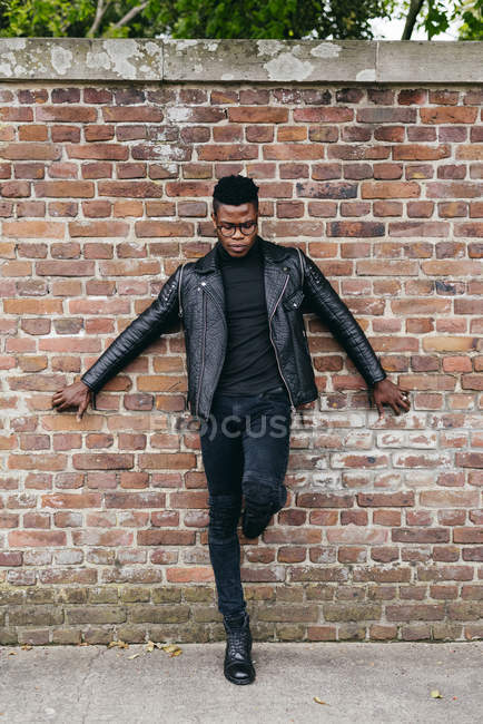 Uomo posa contro muro di mattoni — Foto stock
