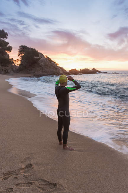 Triathlete standing on sandy beach — Stock Photo