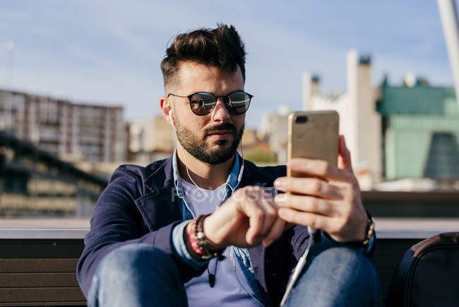 Man relaxing with smartphone on seafront — Stock Photo