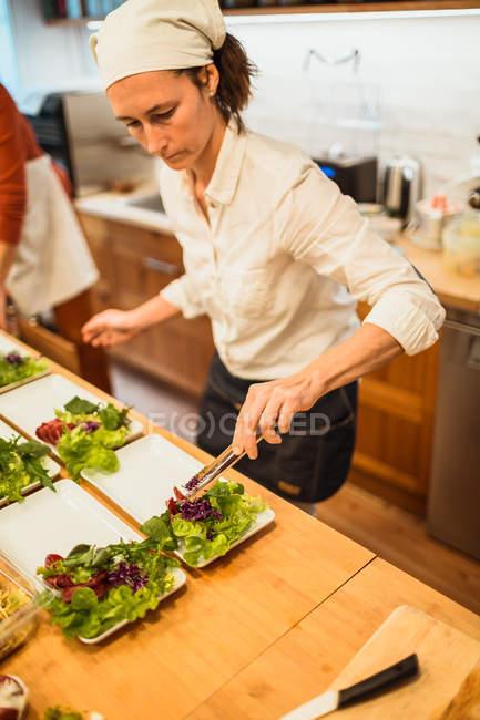 Cuoco che prepara insalata in cucina — Foto stock