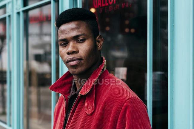 Людина в Червоний жакет стоячи проти кафе — стокове фото