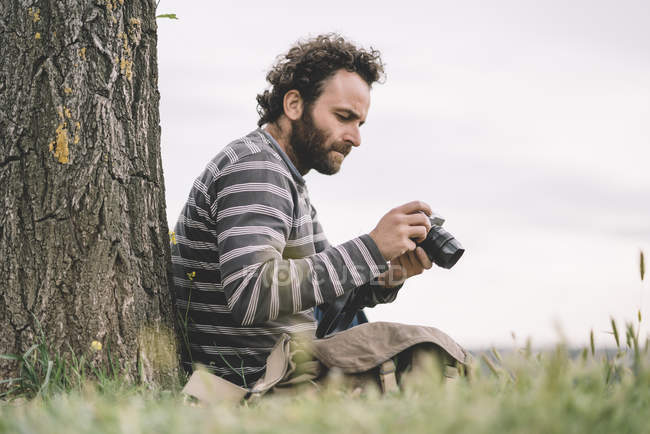Male photojournalist sitting with camera — Stock Photo