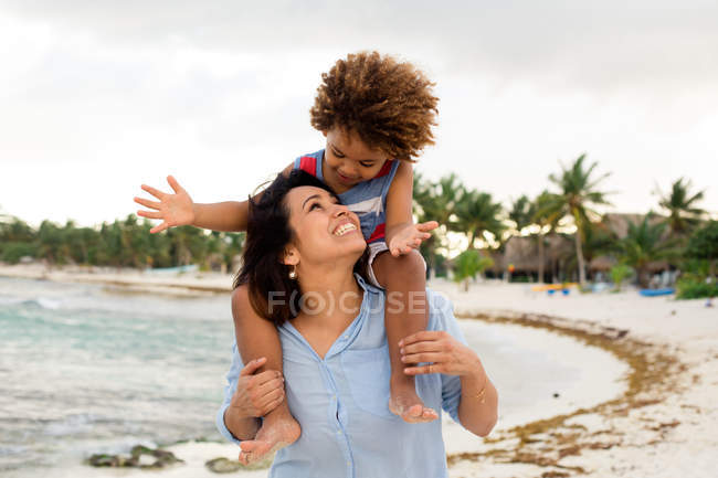 Woman with son on shoulders on beach — Stock Photo