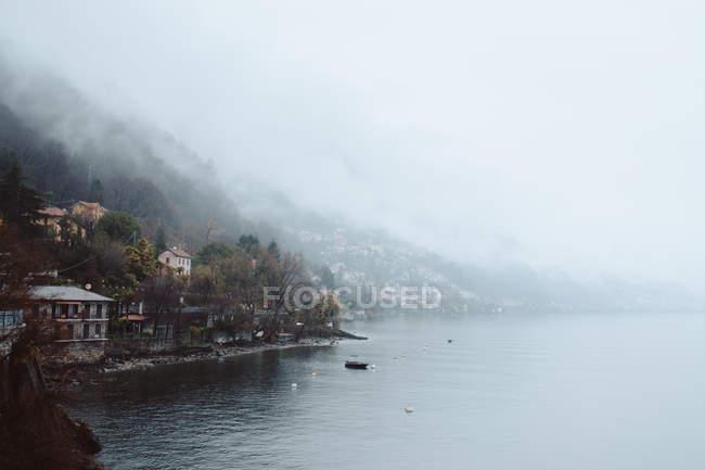 Рыбацкая лодка в озеро и деревне дома — стоковое фото