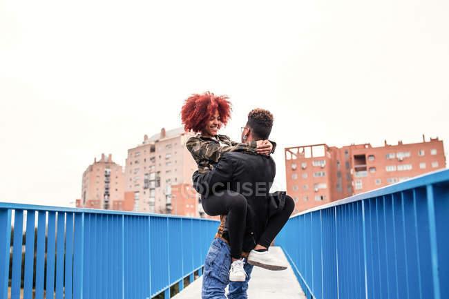 Mann trägt Freundin auf Brücke — Stockfoto