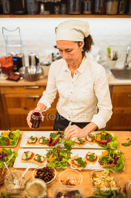 Woman serving plates with vegan snacks — Stock Photo