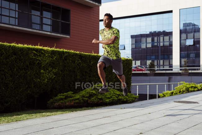 Desportivo étnico homem no salto enquanto correndo na cidade — Fotografia de Stock