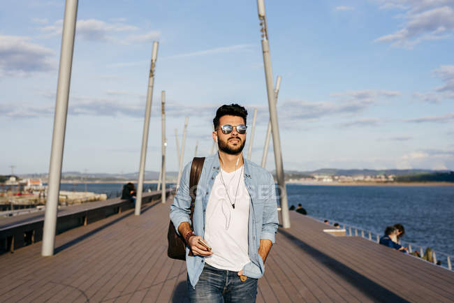Trendy man strolling on waterfront — Stock Photo