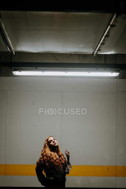 Мрійливий руда жінки куріння перед стіни — стокове фото