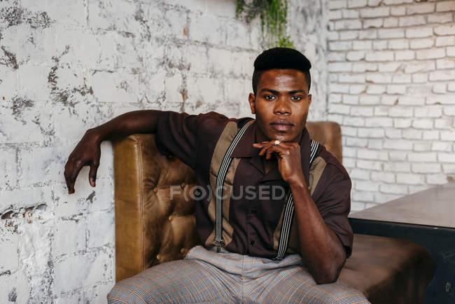 Nero uomo seduto su divano — Foto stock