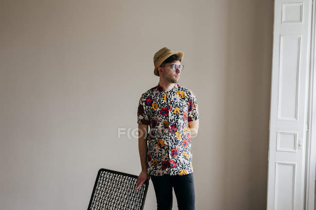 Portrait of stylish man leaning on chair — Stock Photo