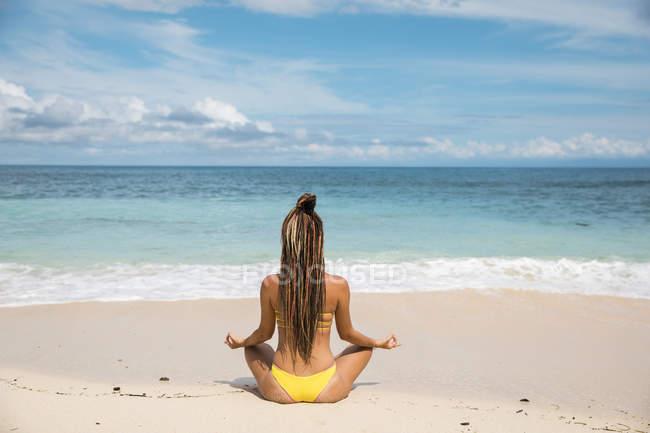 Женщина в бикини медитирует у океана — стоковое фото