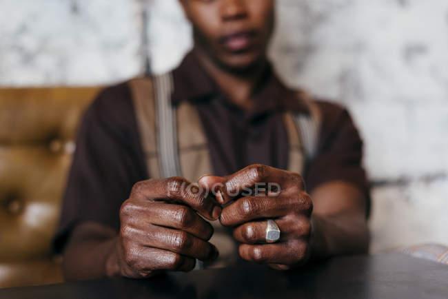 Mani pieghevoli di seduto uomo nero — Foto stock