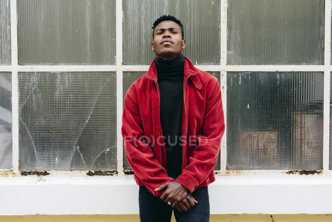 Uomo nero appoggiato sulla parete di vetro — Foto stock