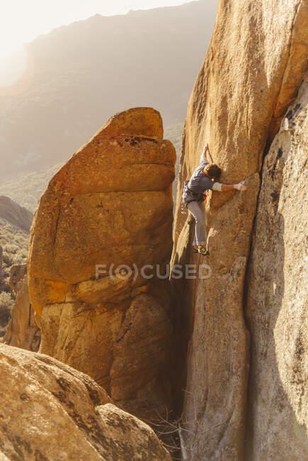 Uomo sportivo che si arrampica su una roccia alle luci della sera. — Foto stock