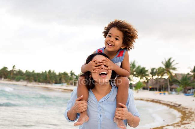 Mulher com o filho nos ombros na praia — Fotografia de Stock