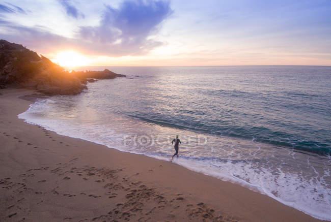 Triathlete running in sea — Stock Photo