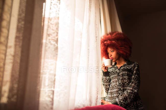 Donna con tazza di caffè vicino alla finestra — Foto stock