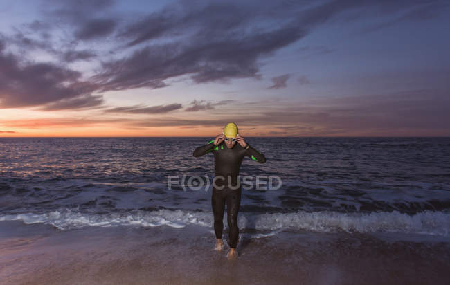 Triathlete walking out of sea water — Stock Photo