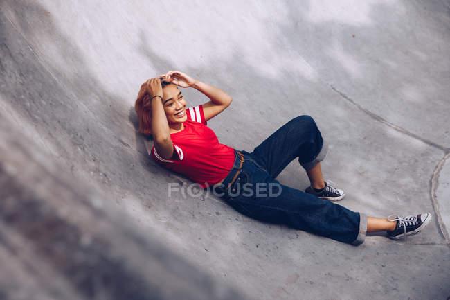 Donna che fissa i capelli e sdraiato sulla rampa — Foto stock
