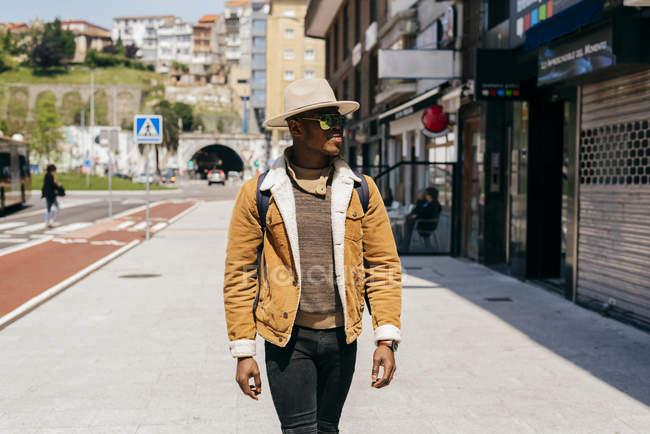 Negro hombre en sombrero y gafas de sol caminando en la calle - foto de stock