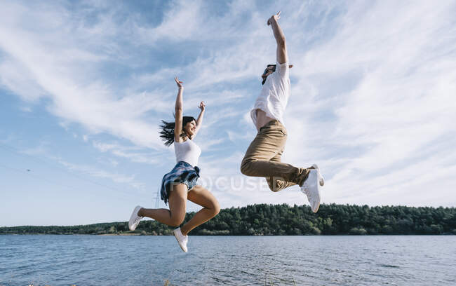 Woman and man in casual clothes having fun on lake and laughing with blue sky and forest on background — Stock Photo