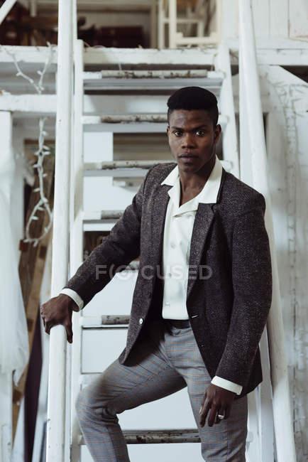 Uomo nero in piedi sulla scala — Foto stock