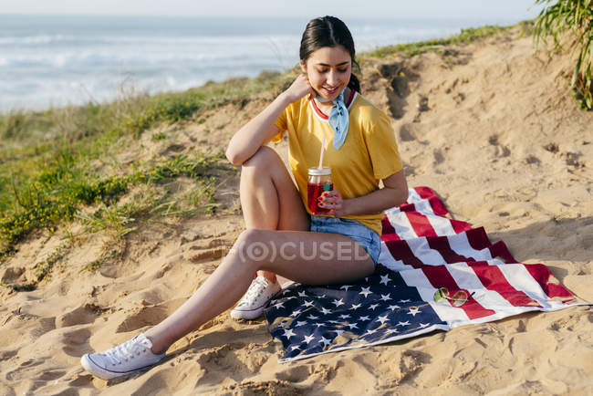 Teenager-Mädchen mit Getränk auf Sand sitzend — Stockfoto