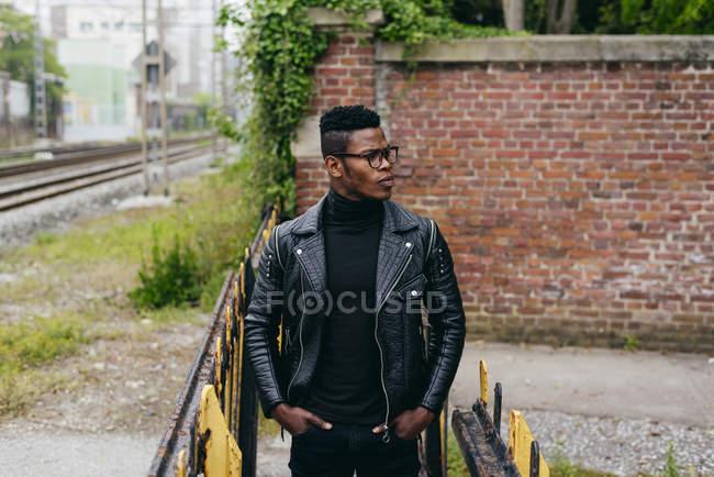 Черный человек, стоящий у перил — стоковое фото