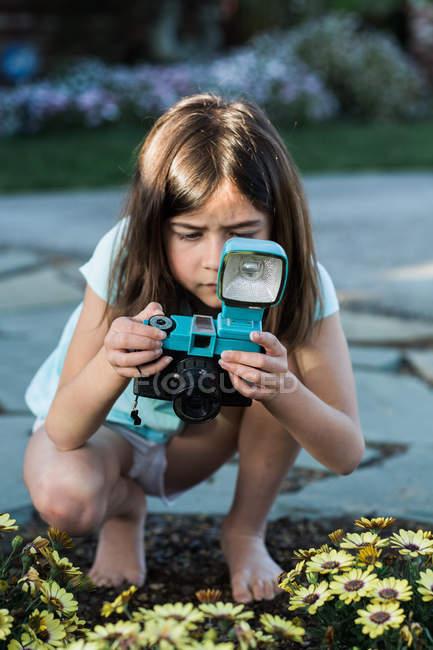 Menina tirando foto de flores — Fotografia de Stock